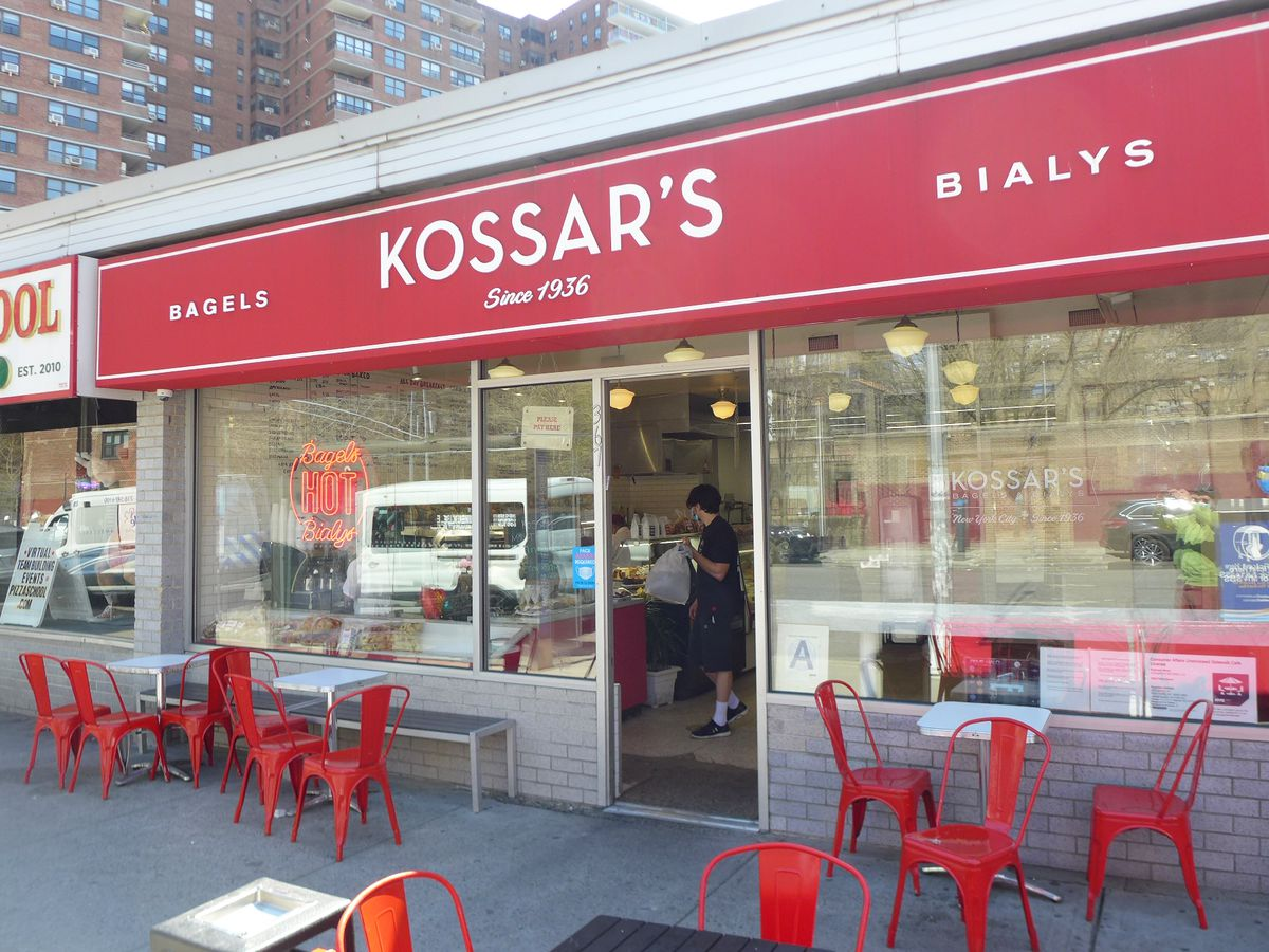 A storefront with a red awning and red patio furniture in front.
