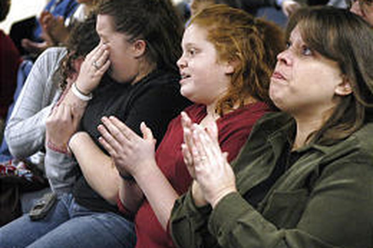 Kalamazoo Central High School seniors Kayla Waldron, left, and Rachael Vondran, seventh-grader Kaitlyn Vondran and Michelle Vondran clap, cry and hug in disbelief Thursday upon hearing that their college tuition would be paid by anonymous donors.