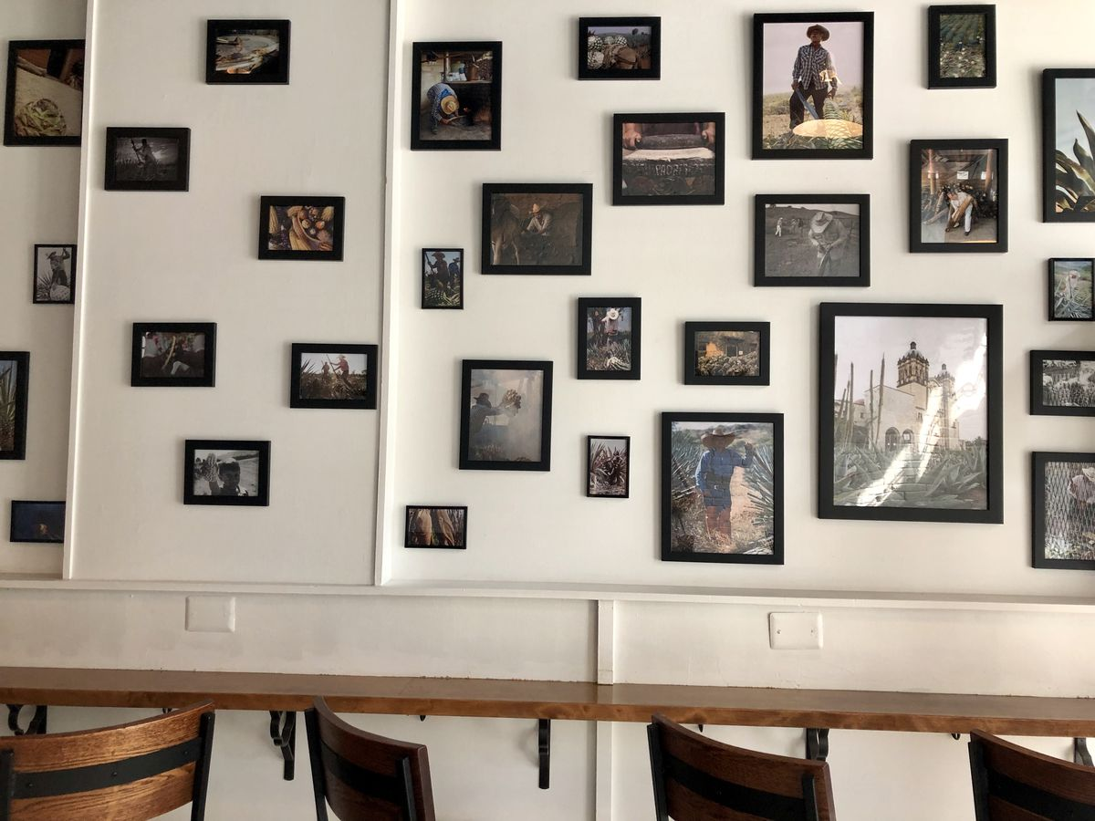 A wall filled with  pictures of Mexican produce and Oaxacan farmers.