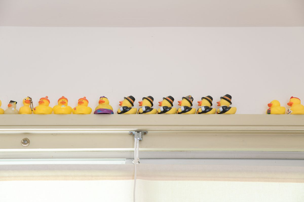 A row of yellow rubber duckies sits on a windowsill in the dining room. Some of the rubber duckies have black top hats.
