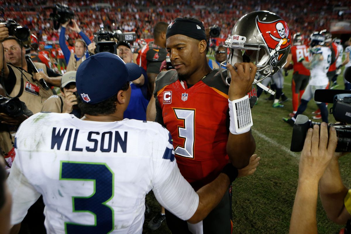 Quarterback Jameis Winston of the Tampa Bay Buccaneers meet up with quarterback Russell Wilson of the Seattle Seahawks in the center of the field following the Bucs'  win over the Seahawks at Raymond James Stadium in Tampa, Florida.