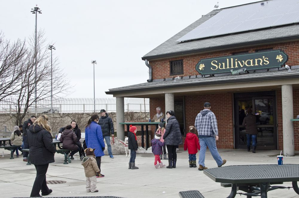 People mill about in front of Sullivan's Castle Island. The restaurant sits at the tip of South Boston.