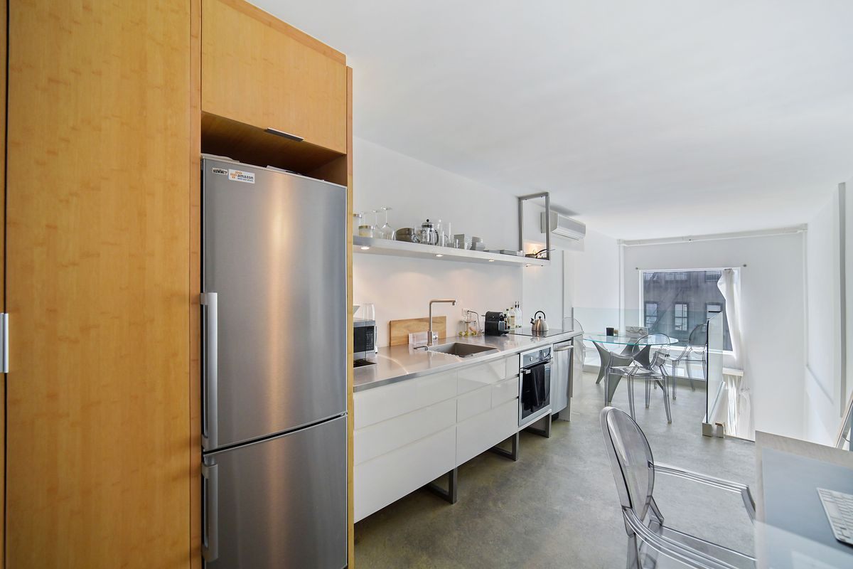 A kitchen with a white shelf and white counters.