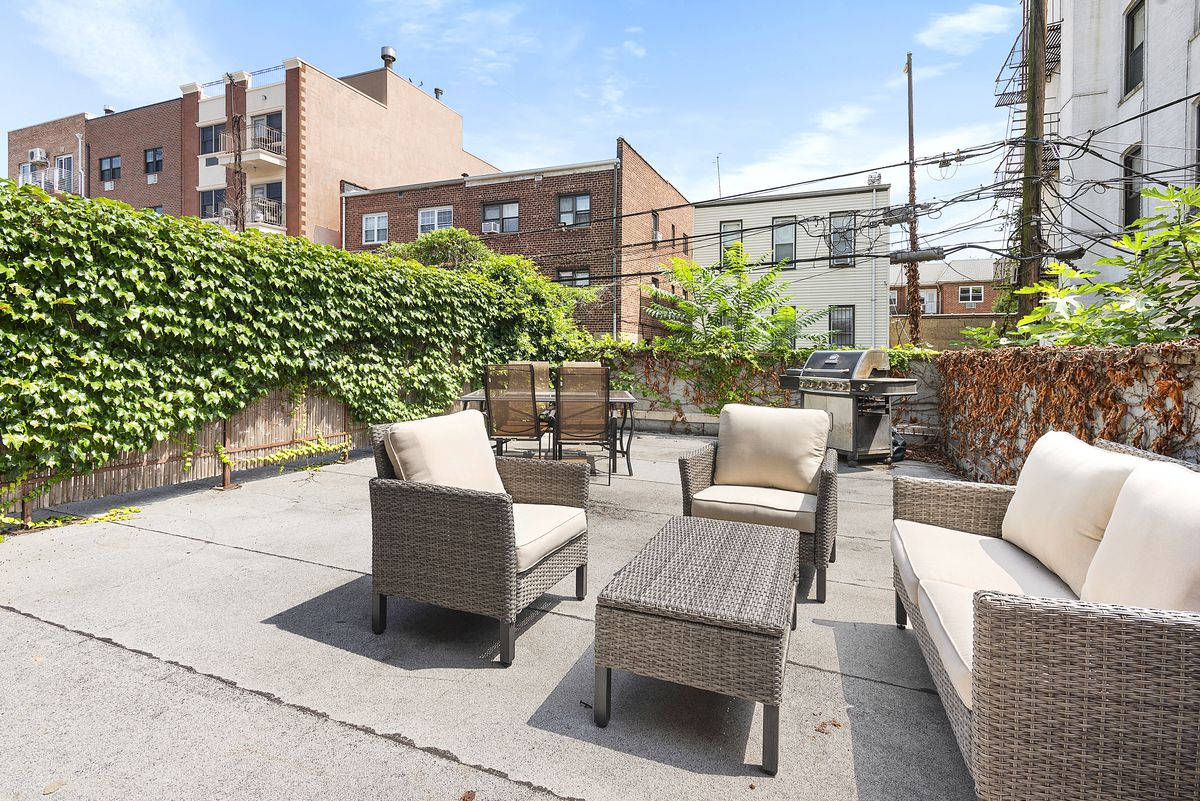 A terrace with two seating areas, a barbecue grill, and ivy-covered fences.