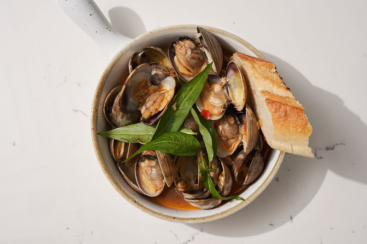 An overhead photograph of a bowl of clams in butter sauce with bay leaves and a slice of baguette