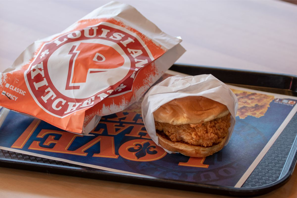 A tray displaying a Popeyes chicken sandwich in a wrapper, next to a bag with the restaurant's logo.