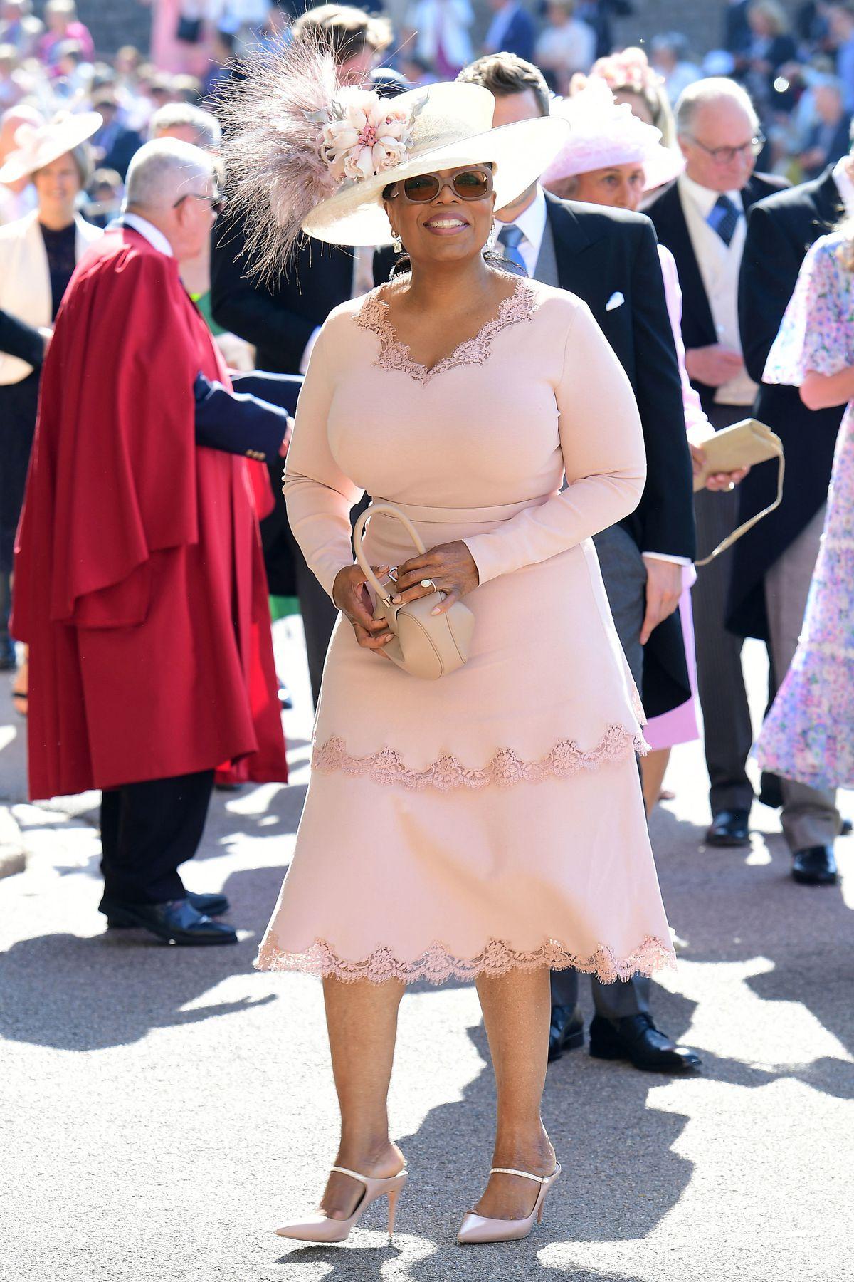 Oprah wears a blush-toned dress.