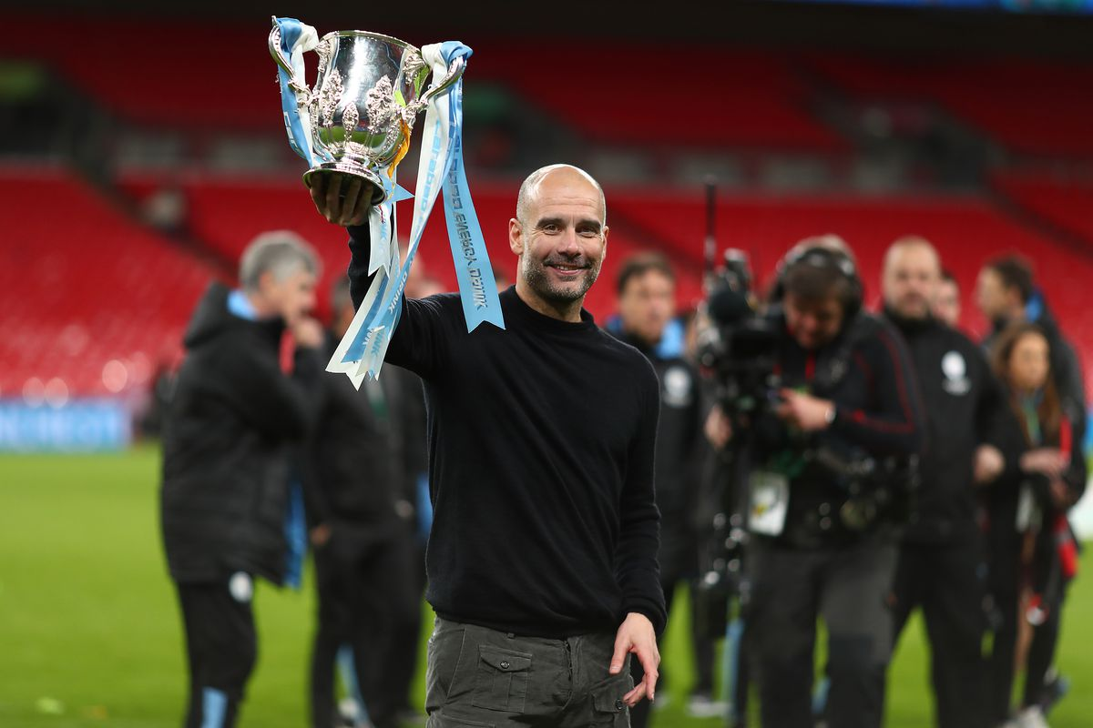 Manager of Manchester City, Pep Guardiola holds the trophy...