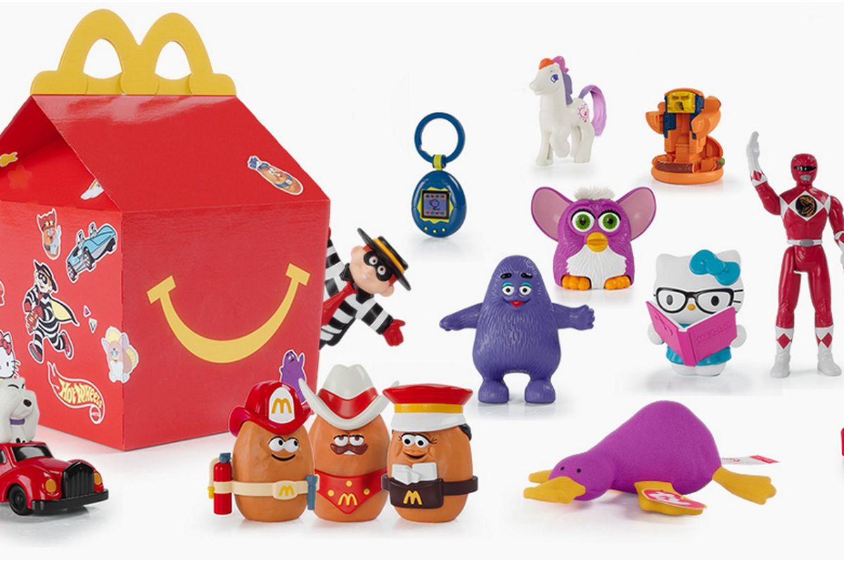 A red Happy Meal box surrounded by toys such as a Furby, Power Ranger, and Hello Kitty