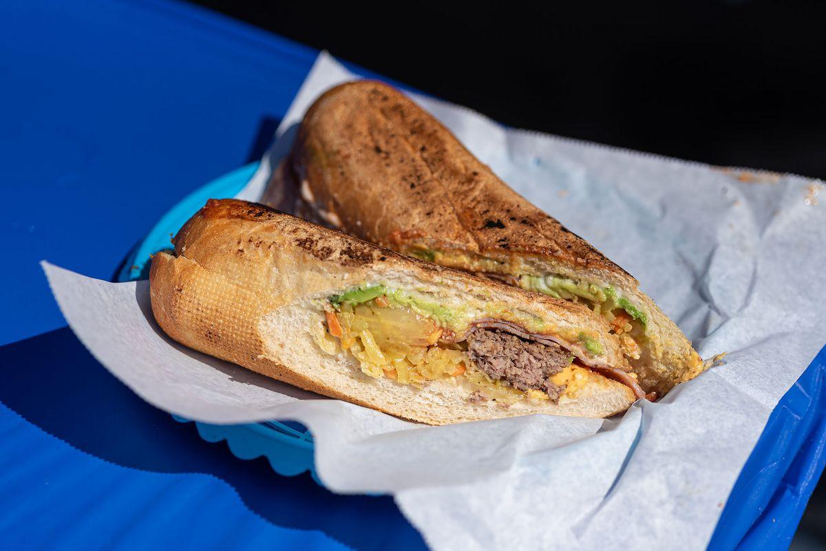 A cross section cut of a long sandwich with burger patties insde.