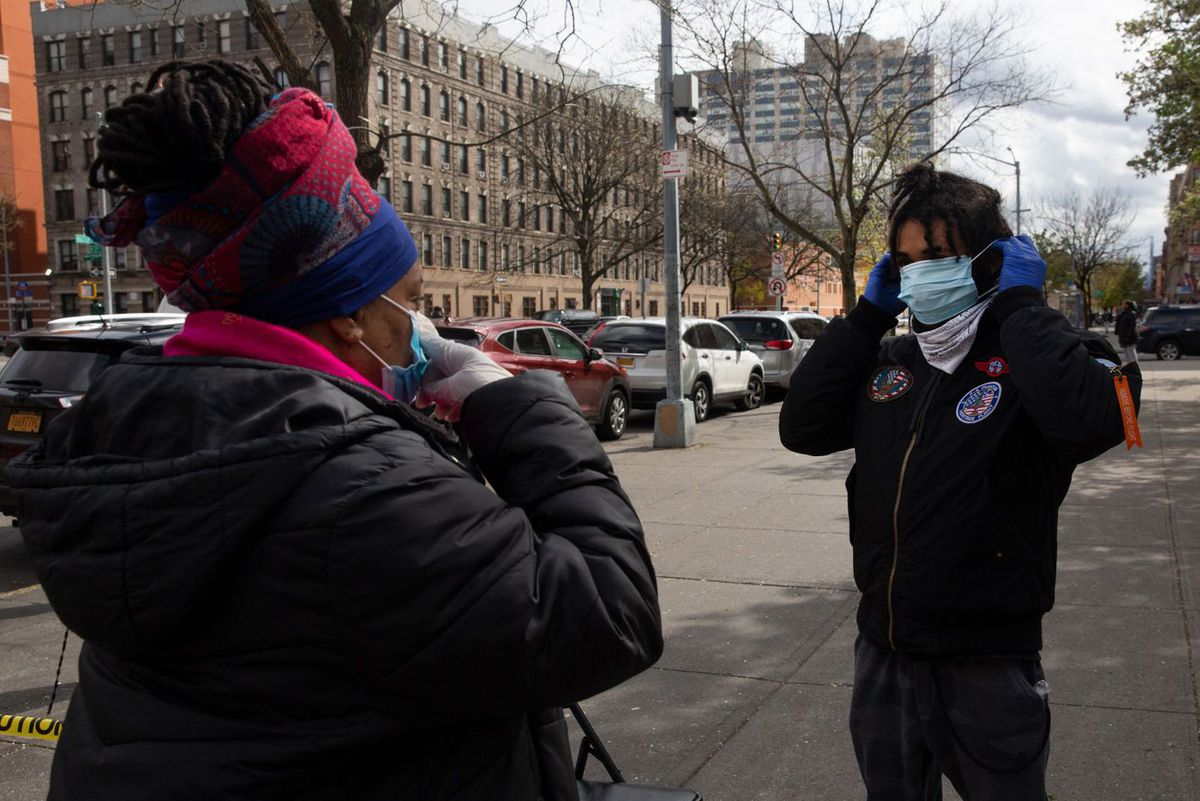 Street Corner Resources founder Iesha Sekou gives a free surgical mask to Thomas Abraham in Harlem during the coronavirus outbreak.