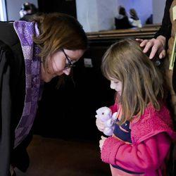 Associate Pastor Rev. Niki Atkinson, left, asks Vida Hines about her stuffed rabbit after Palm Sunday service at First Presbyterian Church in Greensburg, Pa., on Sunday, April 9, 2017.