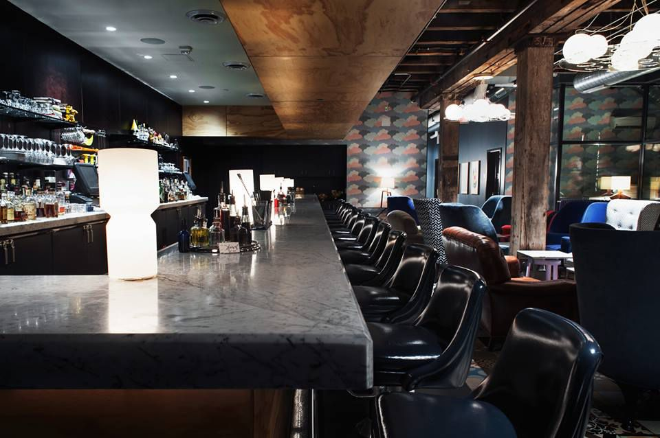 A dark, sexy bar with globe lights and a long line of leather barstools