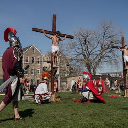 Isaac Bucio, who plays Jesus Christ, acts as if he is crucified during Via Crucis on the field of St. Procopius Catholic Church in Pilsen, Friday morning, April 2, 2021. The annual Via Crucis is a Good Friday tradition that reenacts the Stations of the Cross, a Catholic devotion that recounts Jesus' passion and death.