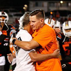 "Weber State football coach Jay Hill hugs Ogden High School coach Erik Thomson during the halftime of high school football game billed as ""Erik Thompson Night"" on Friday, Sept. 3, 2021, at Ogden High School in Ogden."