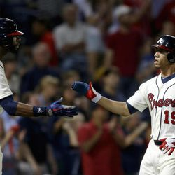 Atlanta Braves' Andrelton Simmons, right, high-fives teammate Jason Heyward after scoring off a double by Martin Prado in the fifth inning of a baseball game against the New York Mets Saturday, Sept. 29, 2012, in Atlanta.