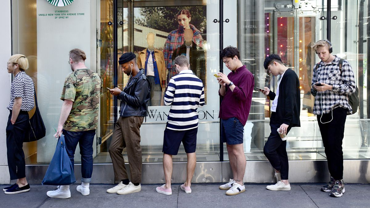 634f6658 A group of men use their phones while waiting for a Uniqlo store to open in New  York City. Photo: Robert Alexander/Getty Images