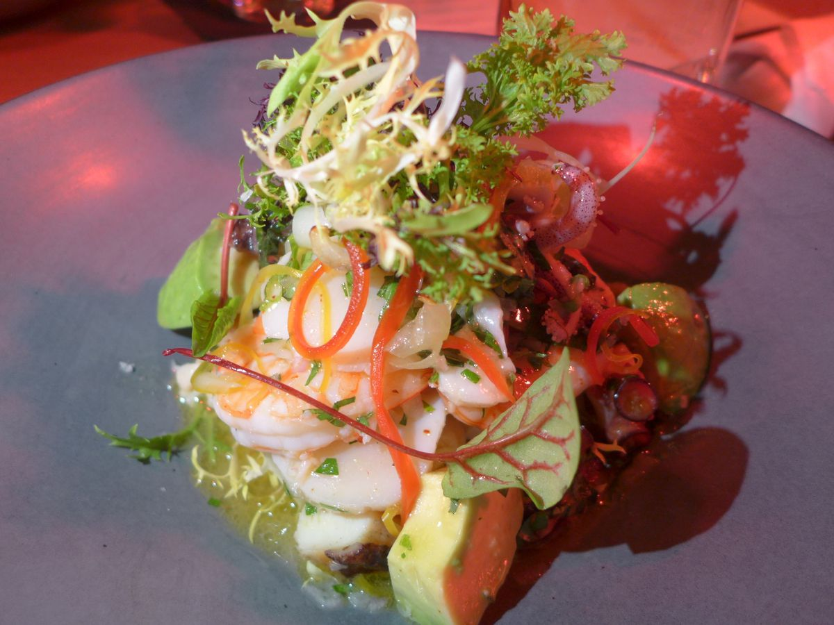 A clump of seafood salad with a sprig of frisee on top.
