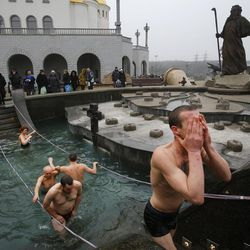 Men get out of the ice cold water after plunging in to mark Epiphany in Minsk, Belarus, on Jan. 19, 2015.