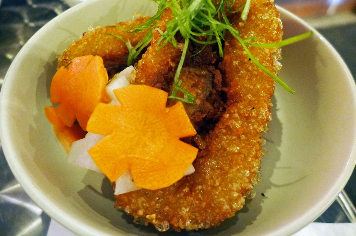 In a white bowl a pair of browned rice cakes with carrots cut like orange flowers on top.