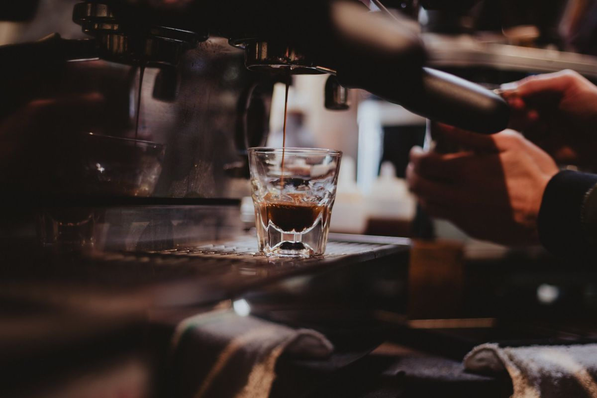 A closeup of a coffee drink being made as a barista works an espresso machine.