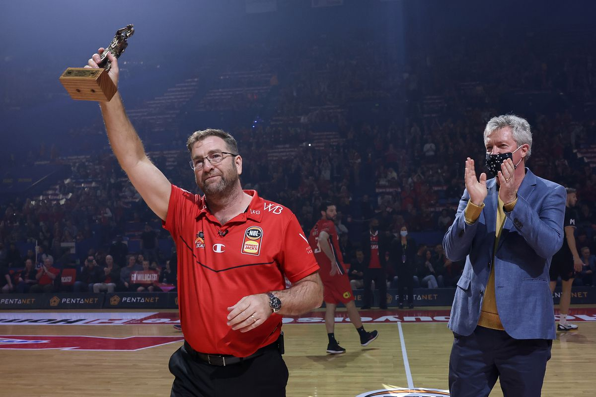 Background:PERTH, AUSTRALIA - JUNE 18: Trevor Gleeson, coach of the Wildcats acknowledges the supporters after being presented the 2021 NBL Coach Of The Year trophy by former Wildcats head coach Alan Black during game one of the NBL Grand Final Series between the Perth Wildcats and Melbourne United at RAC Arena, on June 18, 2021, in Perth, Australia.