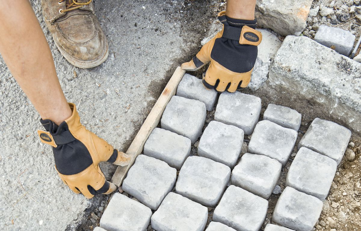Man Places Stake In Between Cobblestone Mat And Driveway Edge As Spacer For Grout