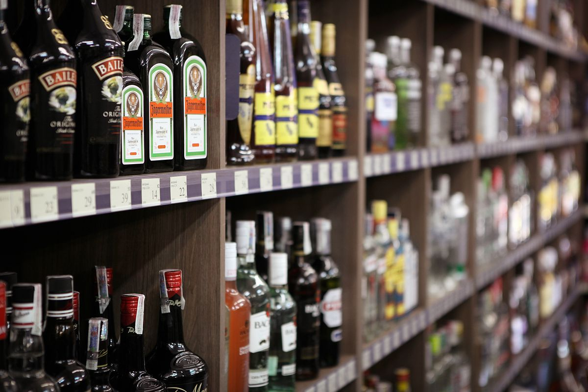 Bottles of Bailey's and Jagermeister sit on brown shelves