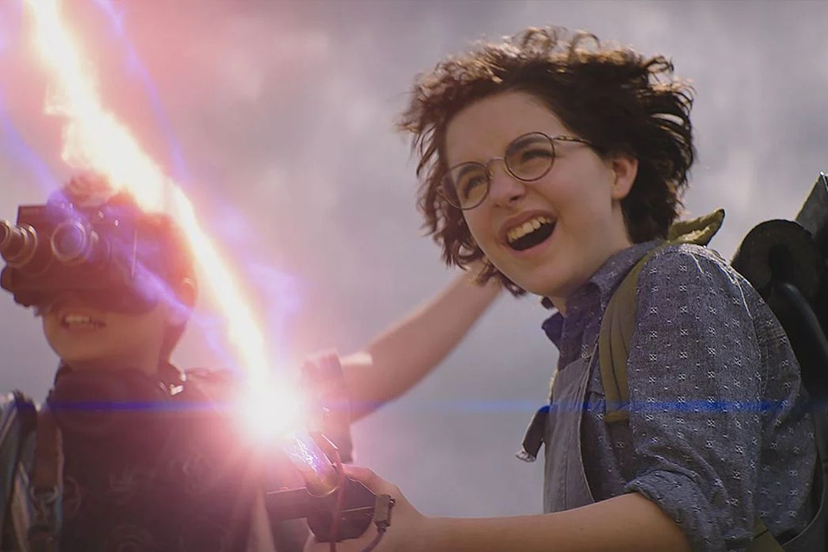 Mckenna Grace wearing goggles and Finn Wolfhard firing a proton pack in Ghostbusters: Afterlife.