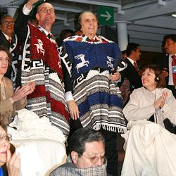 President Thomas S. Monson and President Henry B. Eyring, wearing Mexican serapes to stay warm, salute the crowd inside Mexico City's Aztec Stadium during the LDS Mexican cultural event.