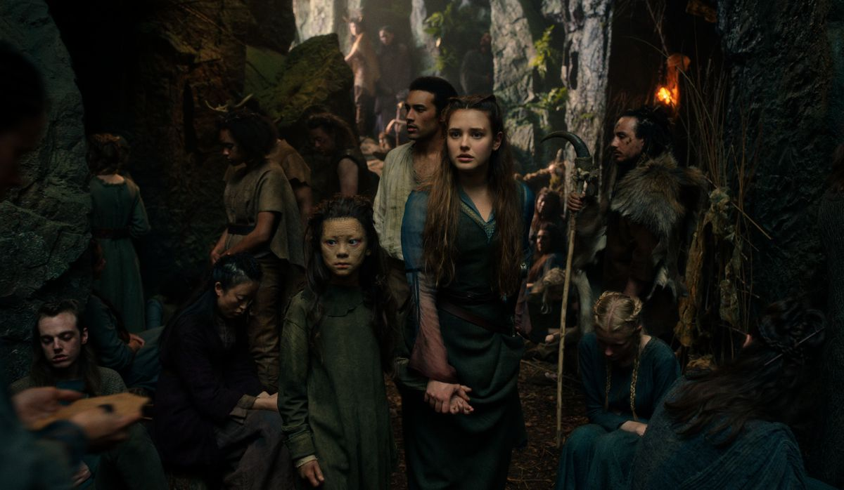 Nimue and Arthur walk through a crowd of people in a wooded village
