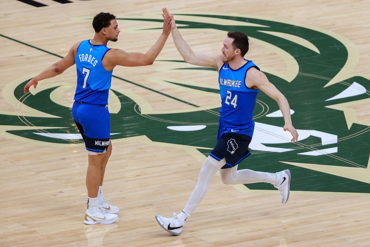 Bryn Forbes #7 and Pat Connaughton #24 of the Milwaukee Bucks celebrate in the first quarter against the Indiana Pacers at the Fiserv Forum on March 22, 2021 in Milwaukee, Wisconsin.