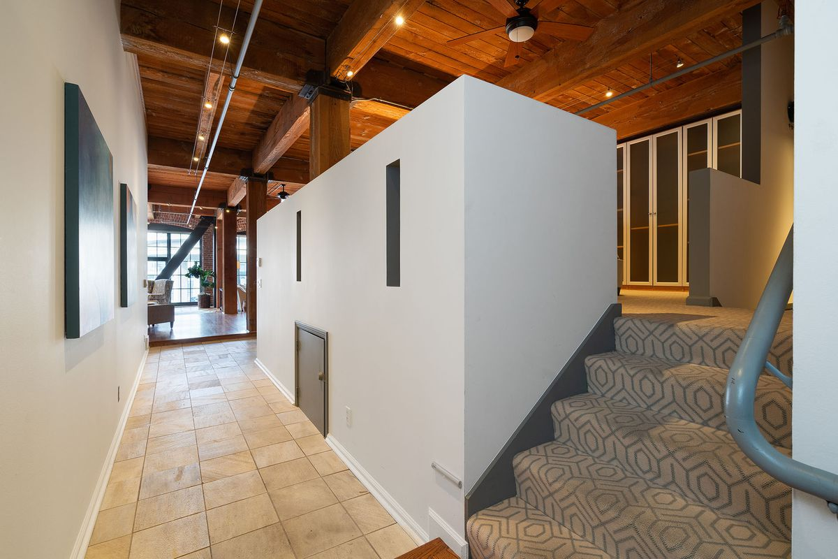 A tiled hallway and gray walls lead to carpeted gray stairs that go to a loft bedroom.