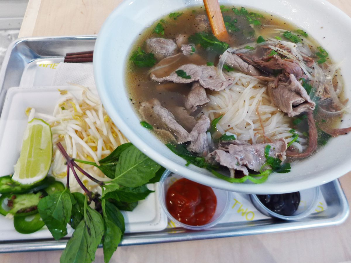 A bowl of beef noodle soup with basil and sprouts on the side.