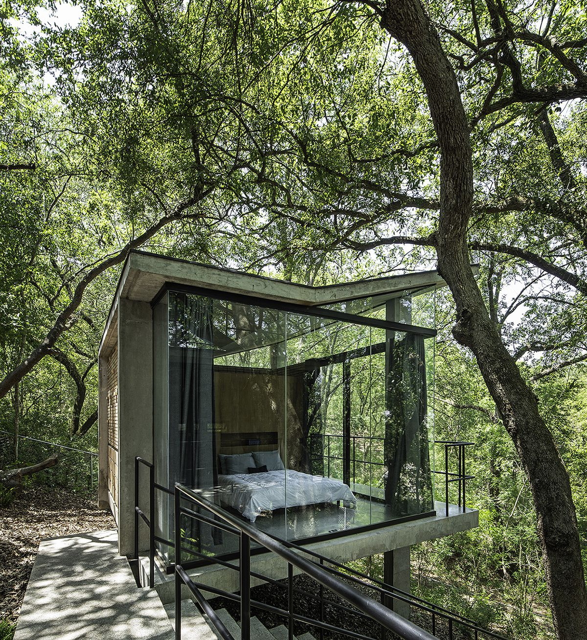 A bedroom encased in glass windows that looks like a treehouse. Trees surround it.