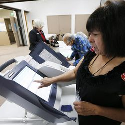 Poll worker Brandy Farmer helps voters at Our Savior's Lutheran Church in Salt Lake County Tuesday, Nov. 4, 2014.