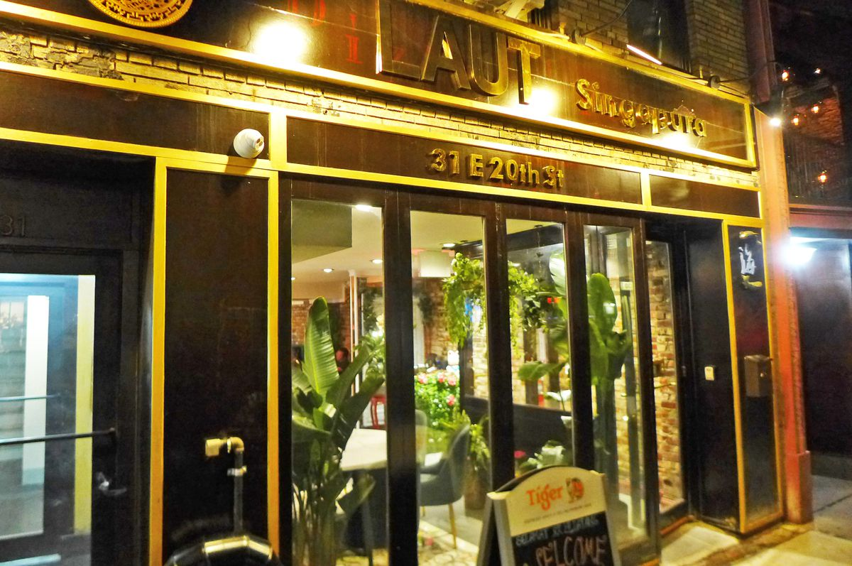 A black facade with gold trim is brightly but badly lit so that it's difficult to make out the name of the restaurant...