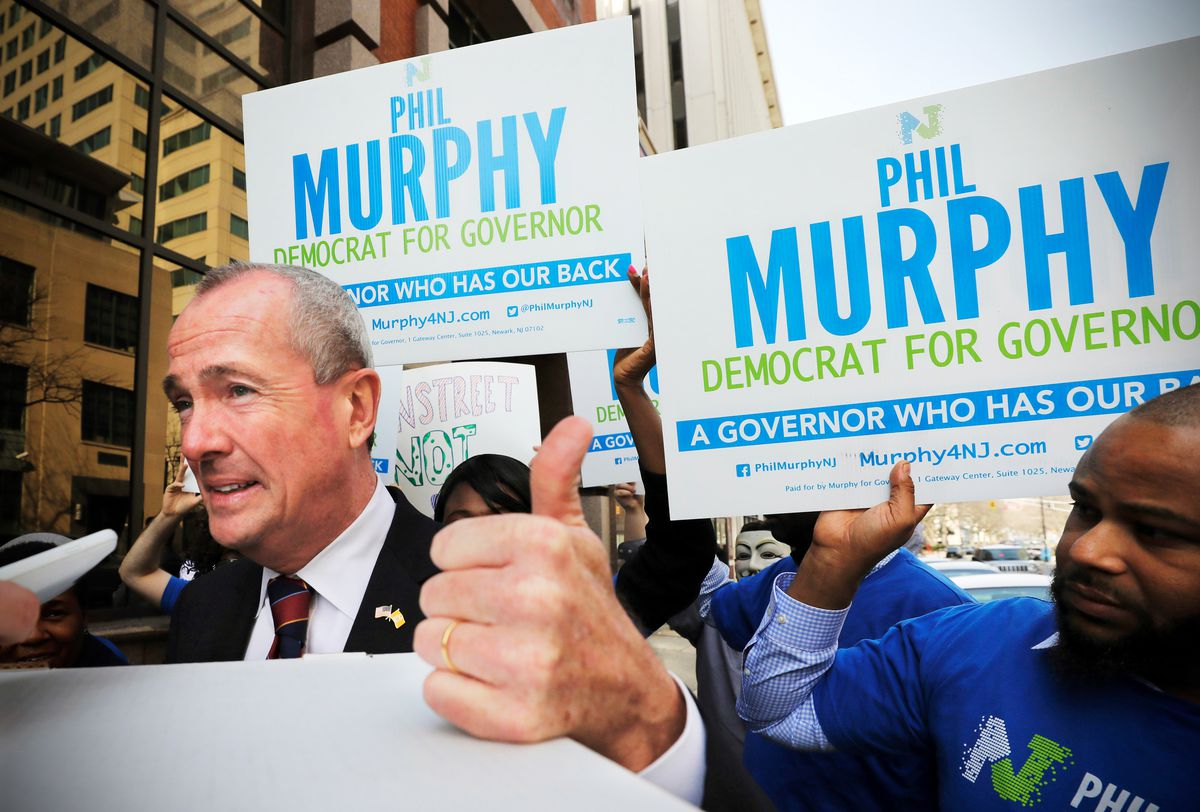 a6df4a2990 Then-New Jersey Democratic gubernatorial candidate Phil Murphy gives a  thumbs-up with supporters behind him as he files a petition to run on April  3, 2017, ...