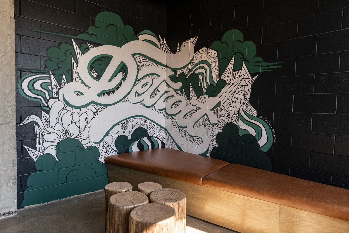 """A brown leather booth with stump tables and a green cinderblock wall painted with a mural spelling """"Detroit."""""""