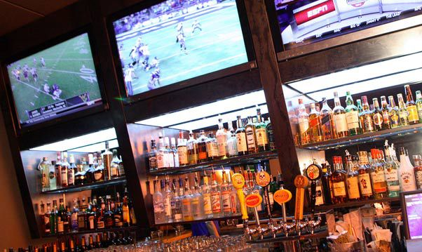 A view of beer taps and an array of liquor bottles at a bar, with a row of TVs above showing football games.