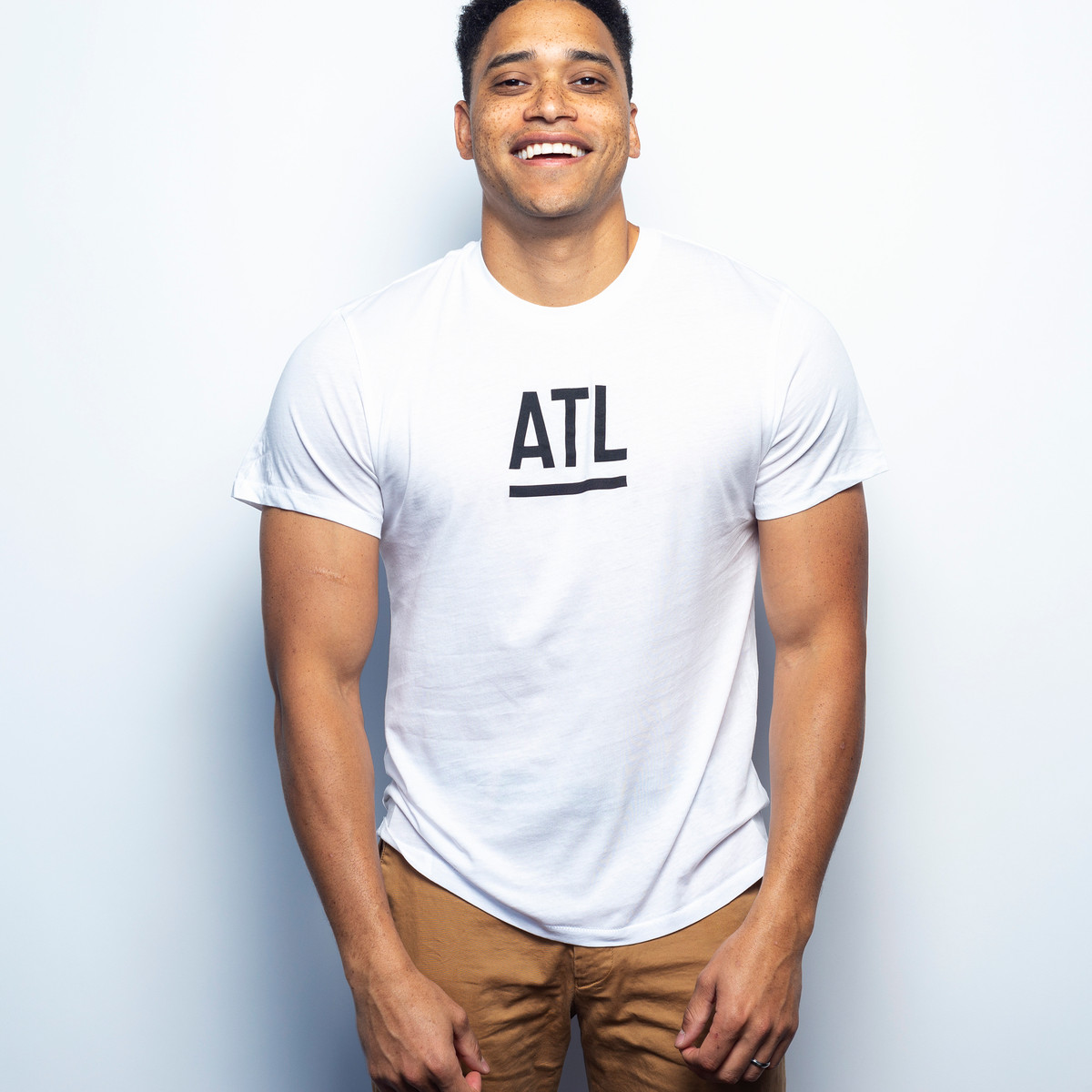 A man smiles at the camera. He is wearing a white t-shirt with black letters which read: ATL.