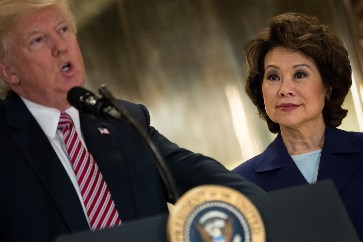 President Trump speaks into a microphone at a podium while Transportation Secretary Elaine Chao stands by.