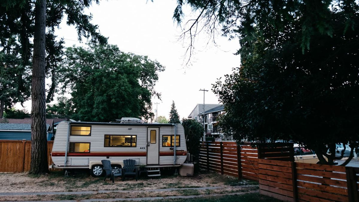 A 1980s camping trailer next to a big evergreen tree in a backyard with a wooden fence. The trailer is white with a horizontal stripe across it in brown tones.
