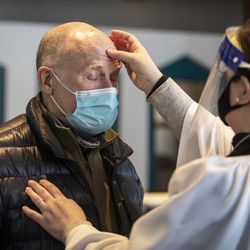 Robert Novickas, 70, of the South Loop, receives the imposition of ashes from the Rev. Amity Carrubba at Grace Episcopal Church of Chicago in the South Loop on Ash Wednesday, Feb. 17, 2021.