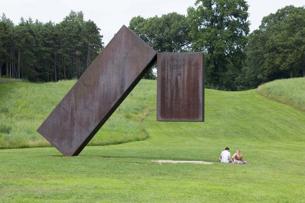 A sculpture sits in the middle of a green lawn. There are two people sitting next to the sculpture. The lawn is surrounded by trees.