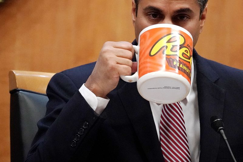 Federal Communications Commission Chairman Ajit Pai drinks from a big coffee cup during a commission meeting December 14, 2017 in Washington, DC.
