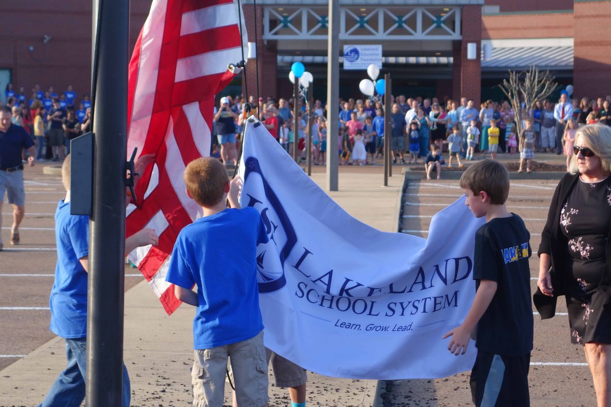 Students raise the Lakeland banner at its ribbon cutting ceremony.