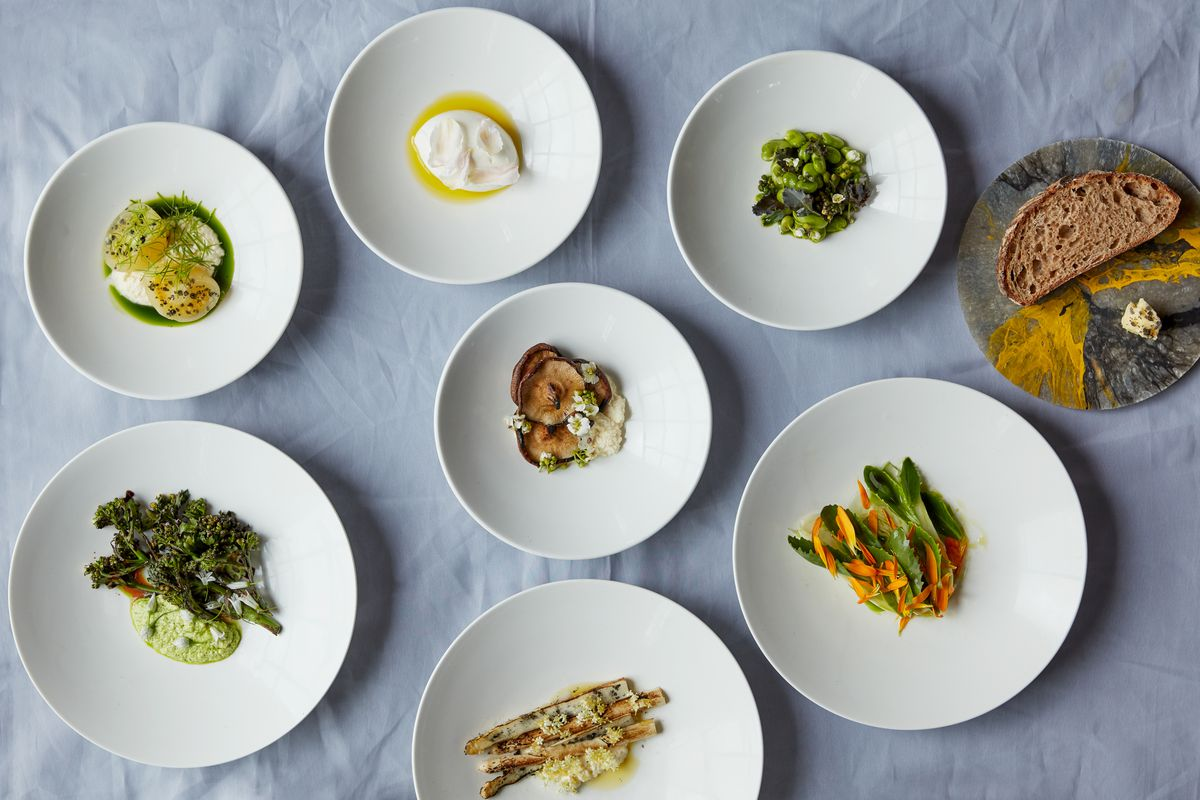 A spread of dishes on white plates and a blue tablecloth at Silo London