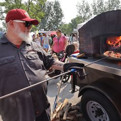 David Kimball cooks a pizza for consumers at the Wheeler Historic Farm farmers market in Murray on Sunday, July 25, 2021.