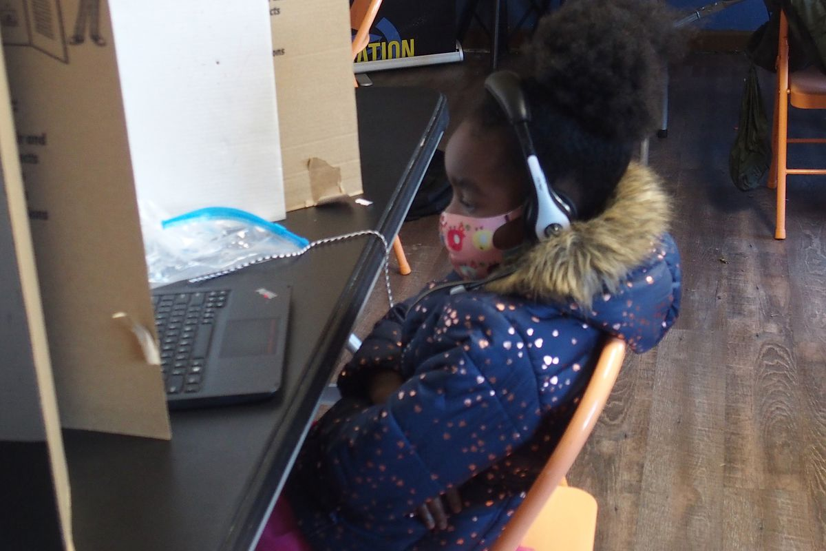 A student in a coat and mask sits with her arms crossed in a metal folding chair at a table with a cardboard divider as she looks at her laptop for her online class.